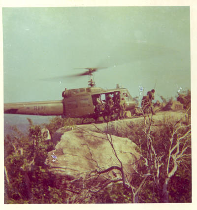 UH-1D clinging to the LZ - W3 had earlier air assaulted the hill top using this rock as the only available LZ    [Binning]